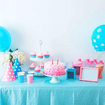 slatki sto - na stolu se nalazi torta, kolaci, dva balona, sokovi